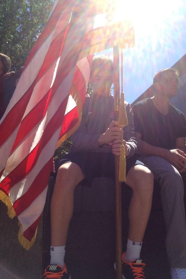 A+student+holds+the+American+flag+during+the+AHS+9%2F11+memorial+ceremony.+