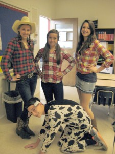 Freshmen cowgirls Jackie Hoege, Madison Myers and Alexis Duday make sure they keep freshman cow Dylan Henderson in line. The students' unplanned thematic costumes were for Thursday's Costume Day.