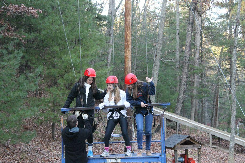 Lacey Gagg, Marissa Phillips, and Rachel Kerl reach for the sky on a free-fall swing at the Young Life Fall Weekend.