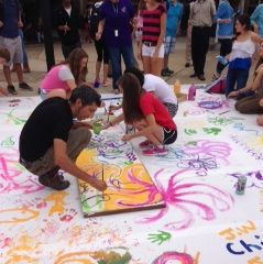 Artist Chicho Lorenzo paints on a canvas surrounded by students' artwork in the Breezeway.