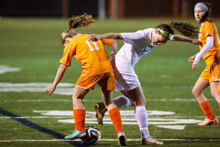 Senior forward Ali Starr is challenged by an opponent during the same game against Orange County. Starr scored 3 of the 8 goals in the team's win against the Hornets.
