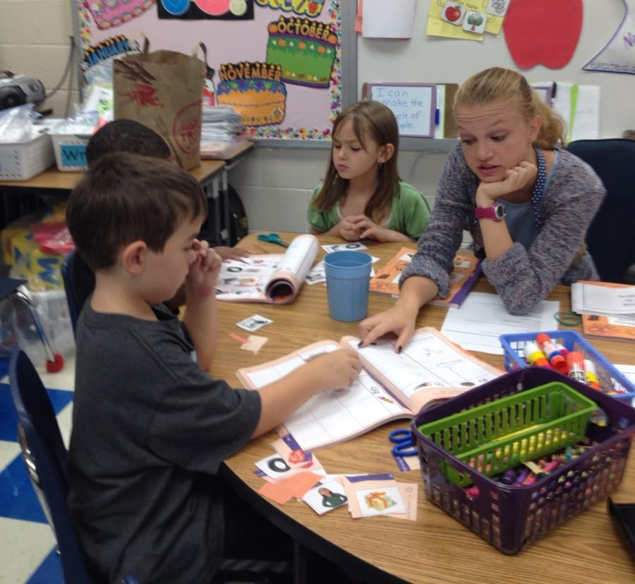 Senior Samantha Muhler works with kindergarteners during her internship at Agnor Hurt Elementary School. Muhler helps children in the classroom's literacy center, teaching them skills such as identifying shapes and writing letters.