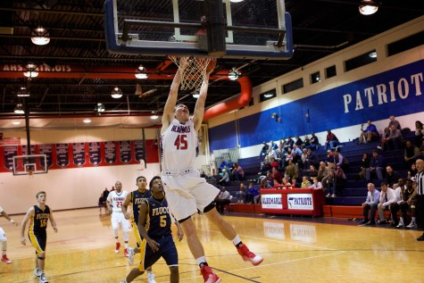 Sophomore Austin Katstra finishes a massive dunk against Fluvanna on Dec. 9. Katstra led the Patriots to a 70-49 victory over the Flucos. Katstra' dunks often motivate the crowd and get them more involved in the game.