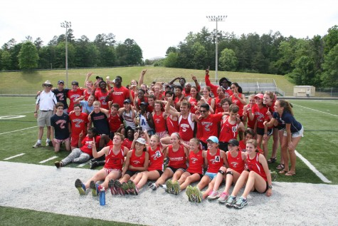 The track team celebrates after the boys narrowly won the conference meet.
