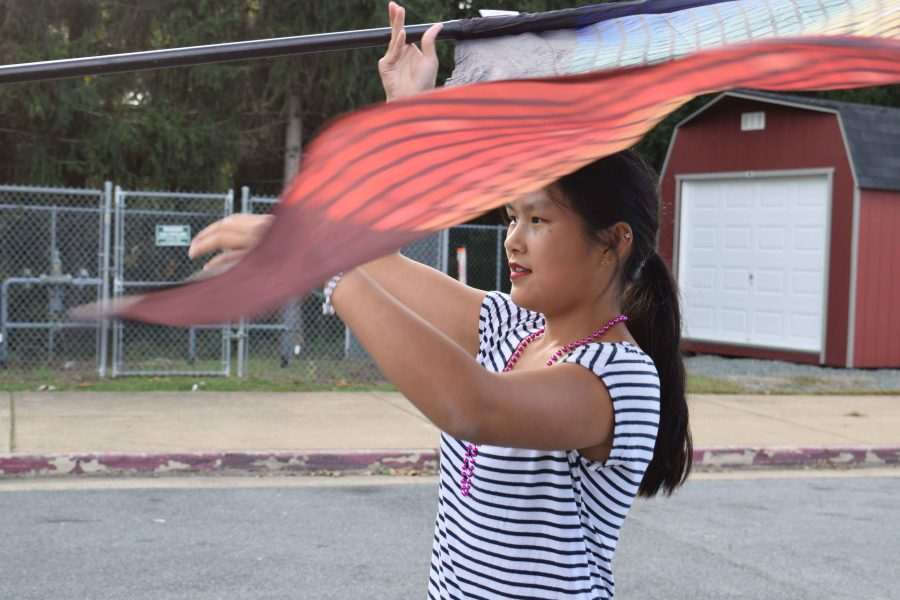 Color Guard member junior Isabella Costabile practices flag twirling before the Homecoming game. After Albemarle beat Fluvanna 41-20, the AHS marching band put on a man-vs.-machine themed performance.