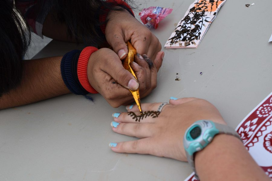 Sophomore Annette Joseph gives a henna tattoo at the Indian Culture Club's booth. Mehndi designs are traditionally worn during Hindu weddings and festivals.