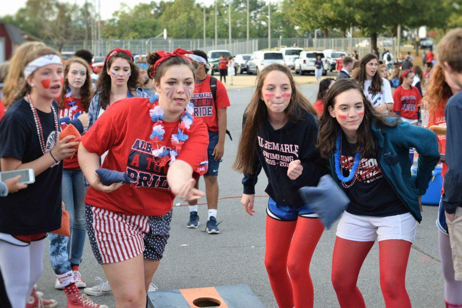Senior Sarah Mills tosses a bean bag in a game of cornhole at the tailgate while her friends stare down the other team.