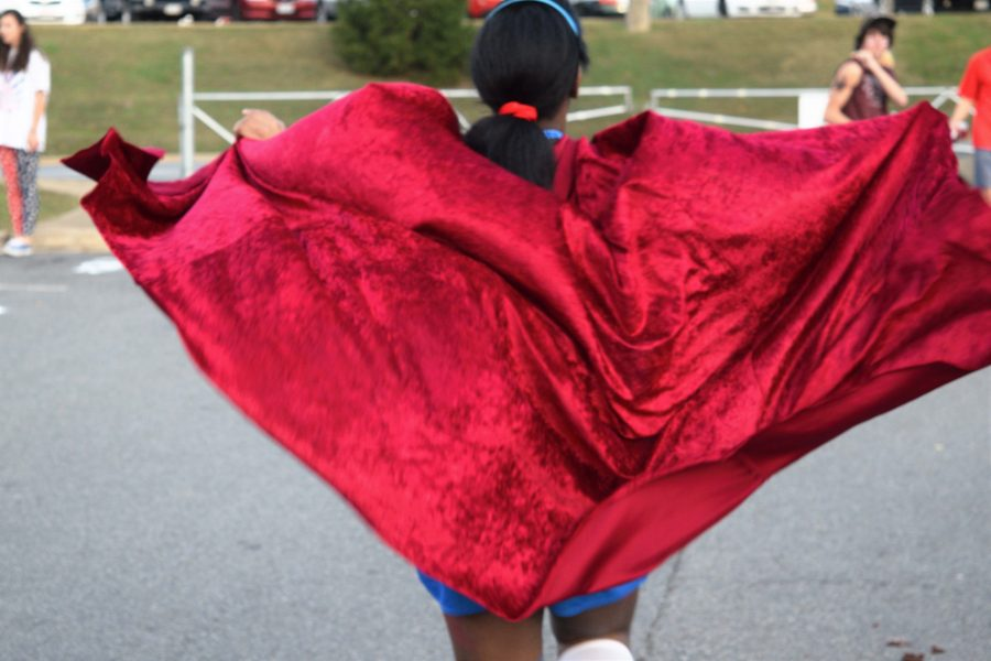 Junior Trinity McDonald's patriotic red cape billows out behind her as she walks through the tailgate.