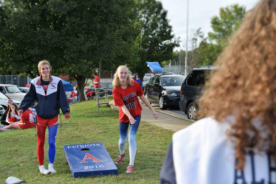 Seniors Emma Weaver and Haley Dillenback play cornhole to the side of the senior parking lot.