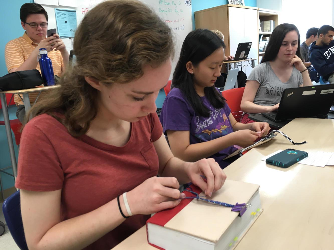 Juniors Mattie Wiseman and Emma Kim make friendship bracelets in their English class. Wiseman has made five bracelets so far this year.