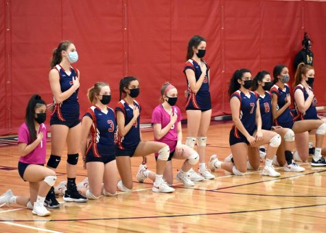 The varsity volleyball team kneels during the national anthem before their March 23 game with Louisa.