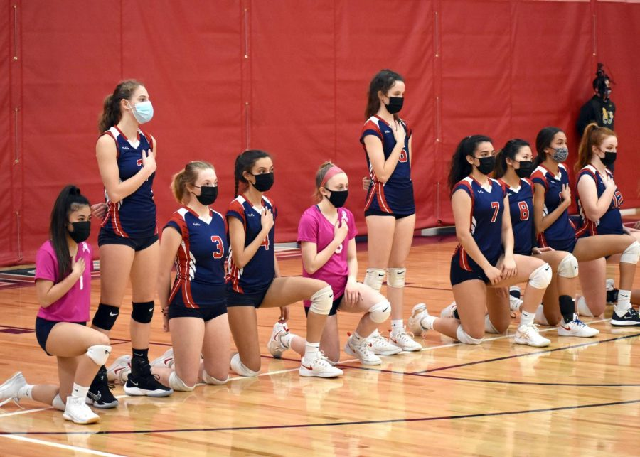 The+varsity+volleyball+team+kneels+during+the+national+anthem+before+their+March+23+game+with+Louisa.+