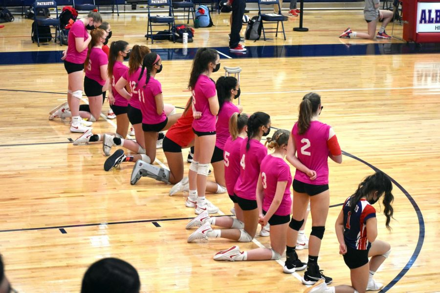 The varsity volleyball team kneels during the national anthem before their March 30 game against Monticello.