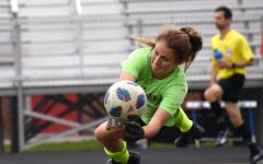 Senior goalie Jaya Daniels stretches to stop a ball during a pre-game practice in 2019.