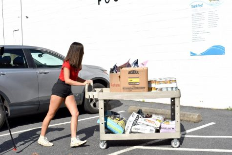 Junior Katharina Ravichandran takes a load of pet food donations to the Loaves & Fishes food pantry in October. Ravichandran started the SWAHg club in response to food insecurity in the Albemarle area.