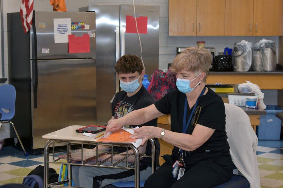 Aide Debra Mills helps senior Joseph Mangard with some paperwork during class.