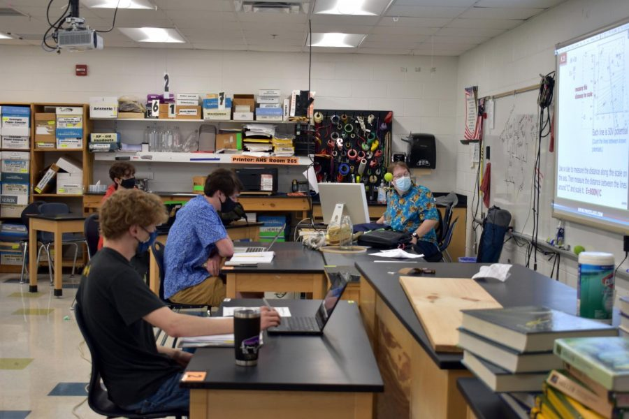 Science teacher Tony Wayne works with his AP Physics 2 students in school.